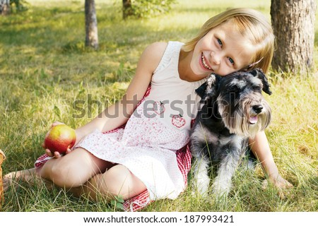 laughing little girl hugging her dog, sitting on green grass in summer garden - stock photo
