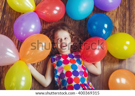 Laughing little girl in birthday party lying on wooden floor. Happy childhood concept. - stock photo