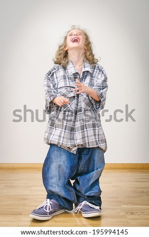 Laughing little girl in oversized jeans and shirt. - stock photo