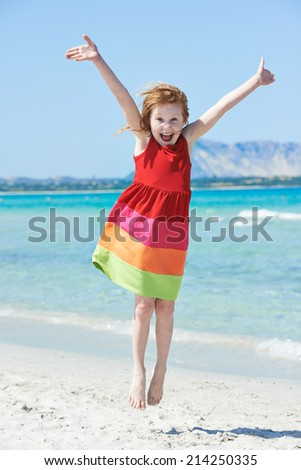 laughing little girl jumping and have fun at summer sea beach - stock photo