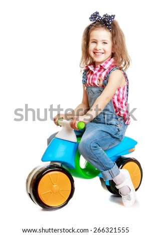 Laughing little girl riding a small bike.- isolated on white background - stock photo