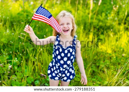 Laughing little girl with long curly blond hair holding american flag and waving it, outdoor portrait on sunny day in summer park. Independence Day, Flag Day concept