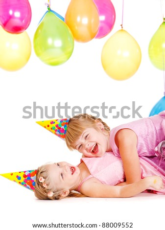 Laughing little girls in party hats playing - stock photo