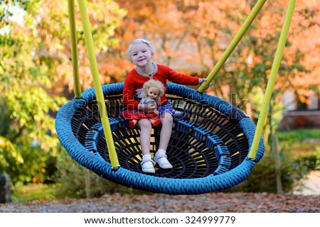 Laughing little kid having fun at playground. Cute blonde toddler girl swinging in the park. Happy children playing outdoors on sunny autumn day. - stock photo