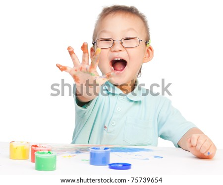 Laughing little painter Chinese boy showing his five with color paint on it - stock photo