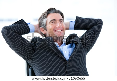 Laughing male executive thinking about his success in his office - stock photo