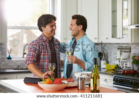 Laughing male gay couple drinking wine and preparing a meal - stock photo