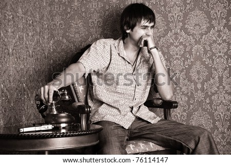 Laughing man sitting beside an antique table, on which the old phone and gun