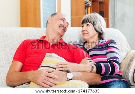 Laughing mature couple relaxing on couch together