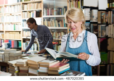 Laughing mature woman reading book while choosing it in book shop