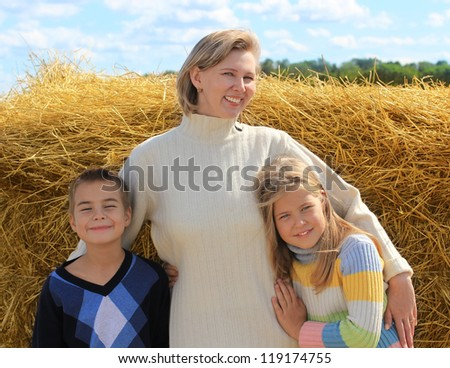 Laughing  middle aged mother  embraces little daughter and son - stock photo