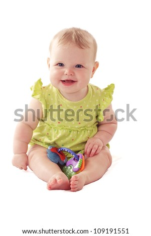 Laughing 6 month old baby girl with big blue eyes and ruffled dress sits holding a rattle. Pastels, isolated on white background, vertical, copy space.