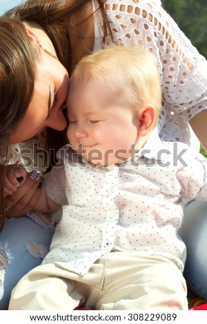 Laughing Mother And Baby outdoors. Nature. Beauty Mum and her Child playing in Park together. Summer Outdoor Portrait of Smiling and Happy family. Joy. Mom and Baby wearing white shirts. - stock photo