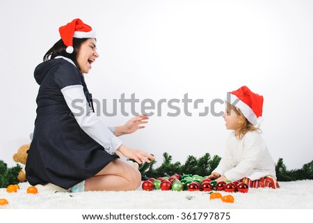 laughing mother and daughter playing with christmas balls - stock photo