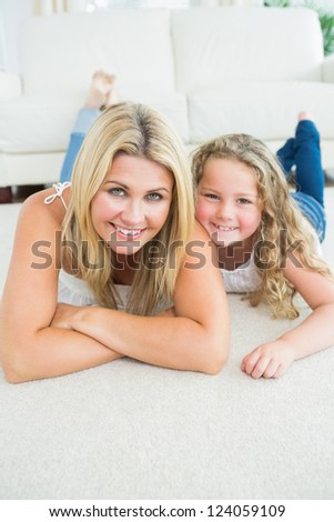 Laughing mother and daughter resting on the white carpet - stock photo