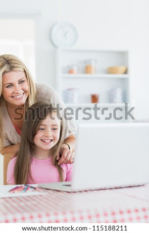 Laughing mother and girl looking at laptop in the kitchen - stock photo