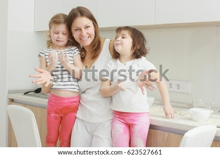Laughing mother and her daughters in the kitchen in home clothes