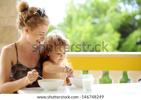 Laughing mother and her son having breakfast on outdoor terrace with handrail and columns on natural background.