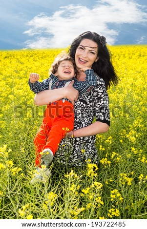 Laughing mother and toddler son in canola field  - stock photo