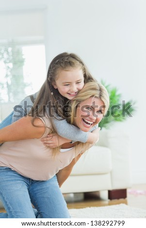 Laughing mother giving daughter a piggy bank in the living room - stock photo