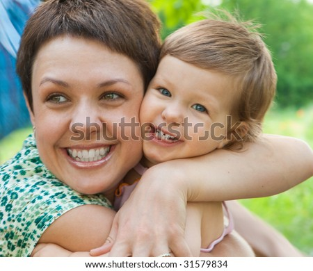 Laughing mother hugs her dearest baby - stock photo