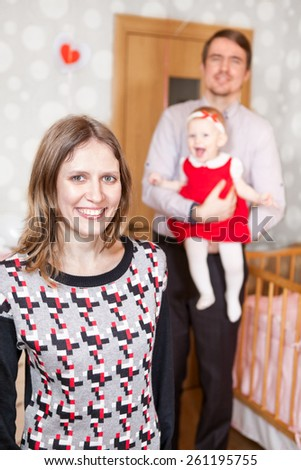 Laughing mother standing on foreground with father and baby on background - stock photo