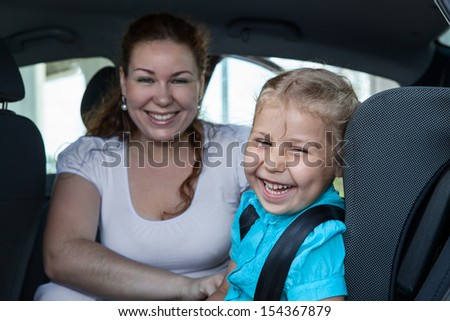 Laughing mother with small daughter in car safety seat - stock photo