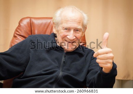 laughing old man sitting in a chair showing thumbs up - stock photo