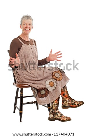 Laughing older woman with short gray hair sits sideways on chair with hands outspread. She wears flowered boots and brown cotton shift dress. Isolated on white background, vertical, copy space.