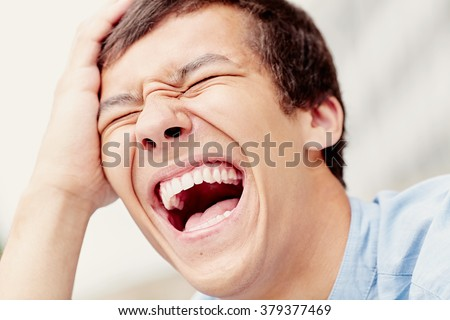 Laughing out loud young man face closeup outdoors -  laughter is best medicine concept - stock photo