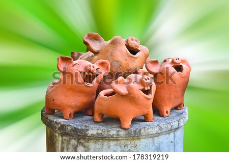 Laughing pig statue on nature abstract - stock photo