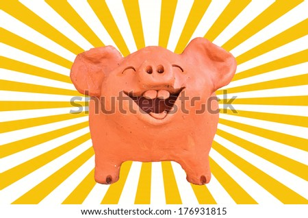 Laughing pig statue on sun beam - stock photo