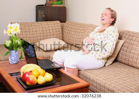 Laughing pregnant woman near the laptop - stock photo