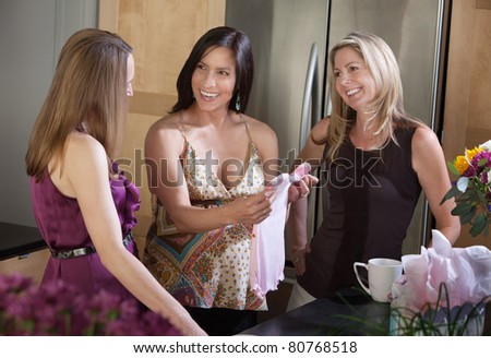 Laughing pregnant woman with friends holds baby clothes in kitchen - stock photo