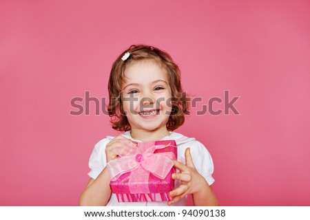 Laughing preschool girl holding small gift box - stock photo