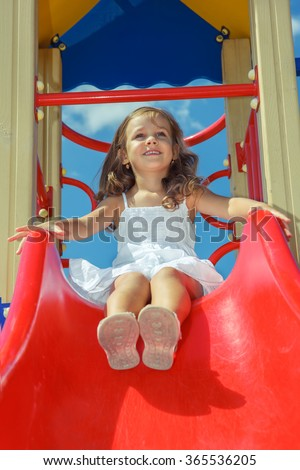 Laughing preschool girl sitting on the top of a kids slide, at the playground