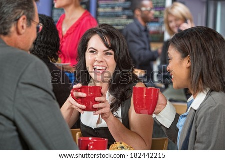 Laughing pretty woman with friends in coffee house - stock photo