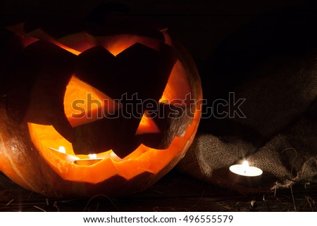 Laughing pumpkin Halloween Jack-o'-lantern in the hay on a dark wooden background instead of with a candle