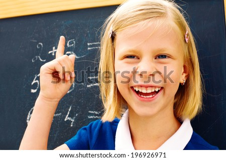 laughing schoolgirl found the correct solution of a mathematical problem - stock photo