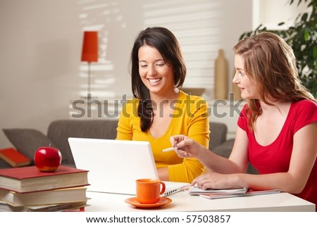 Laughing schoolgirls looking at laptop, blond girl pointing at screen.? - stock photo