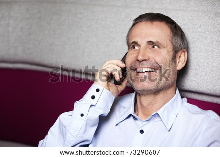 Laughing senior businessman in blue shirt sitting on sofa and talking on mobile phone. - stock photo