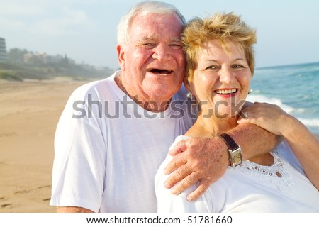 laughing senior couple hugging on beach - stock photo