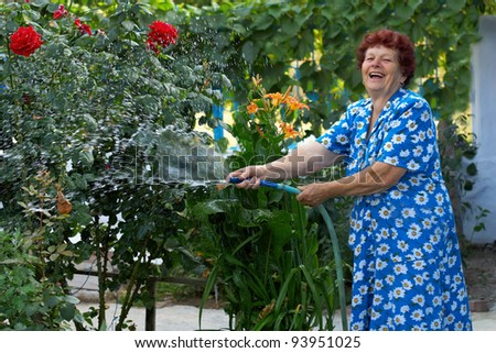 laughing senior woman in colorful dress irrigating flower garden - stock photo