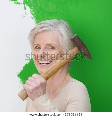 Laughing senior woman with a vivacious smile doing interior decorating at home standing with a hammer in front of a half painted green wall - stock photo