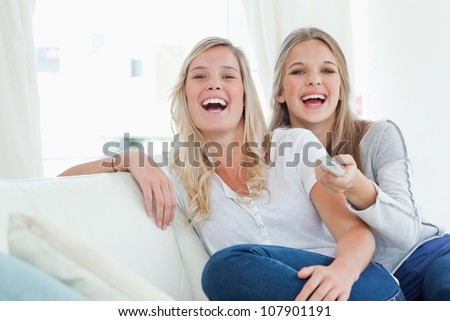 Laughing sisters on the couch as they watch tv and look at the camera - stock photo