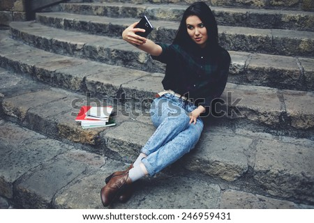 Laughing student girl taking a self portrait with smart phone sitting on steps, beautiful hipster girl photographing herself with mobile phone, charming girl smiling while taking a self-ie outdoors - stock photo