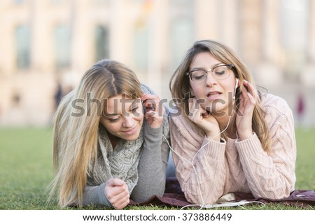 Laughing student girls with earphones lying on grass - stock photo