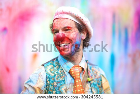 Laughing stylish clown splattered with paint - stock photo