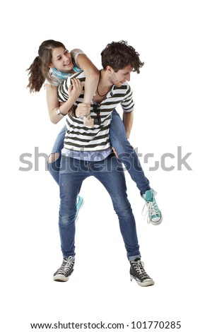 Laughing teen girl playfully jumps up on teen boy's back. Both wear stripes, jeans, and sneakers. Vertical, isolated on white, copy space. - stock photo
