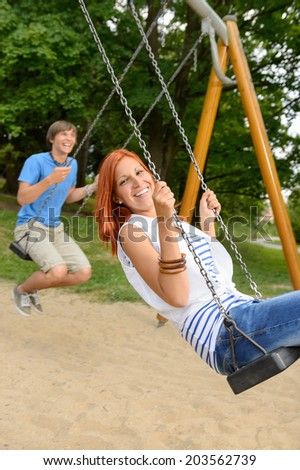 Laughing teenage couple on swing in park have fun together - stock photo